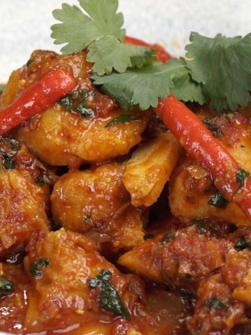 A close up view of Burmese fish curry garnish with coriander and sliced red chilli.