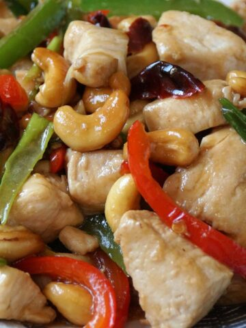A close up view of chicken stir fry with cashew nuts and vegetables.