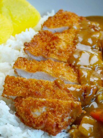 Japanese style crispy chicken on the white rice and curry sauce one side of the plate.