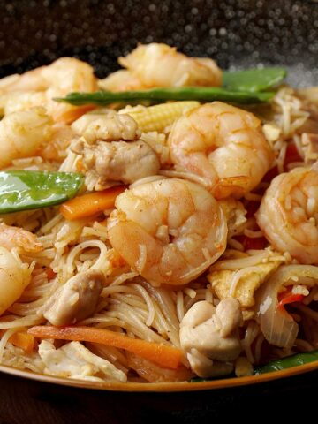 A close up view of Singaporean style noodle topped with shrimp and chicken.