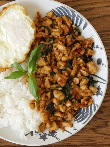 A plate of white rice topped with spicy basil chicken and fried egg and garnish with basil leaves.
