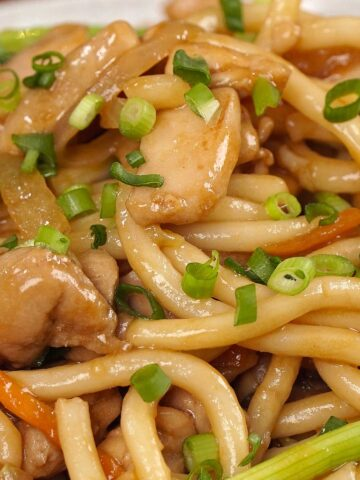 A close up view of Japanese udon noodles stir fry garnish with chopped spring onions.