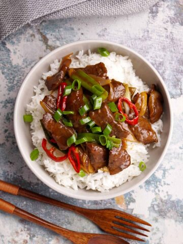 Mongolian stir fry beef on the white rice in the white colour bowl with wooden fork and spoon next to it.