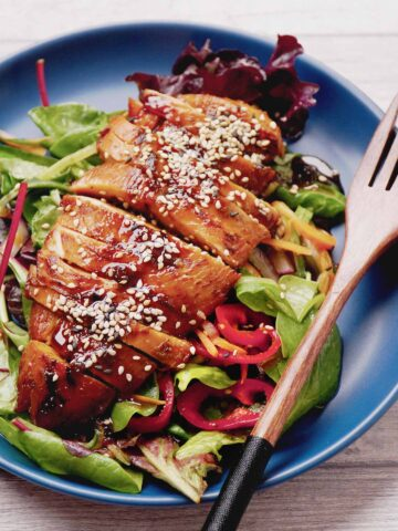 Thai style grilled chicken on the bed of green salad are on the blue plate.