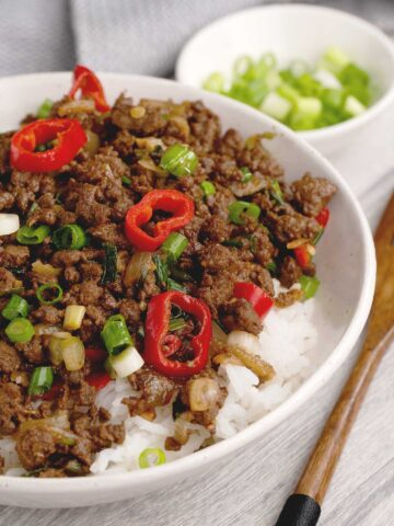 A bowl full of mongolian beef topped with sliced chilli and a small bowl of sliced green onion in the background.