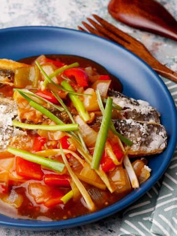 Fried seabass fish in sweet chilli sauce topped with shredded green onion on the blue plate.