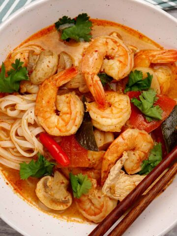 A bowl of thai style soup with spicy broth topped with shrimp, chicken and tomatoes garnish with sprinkle of coriander, with wooden chopstick on the bowl.