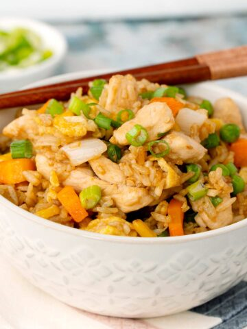 A bowl full of chicken fried rice with sprinkle with green onions with wooden chop stick on the side.