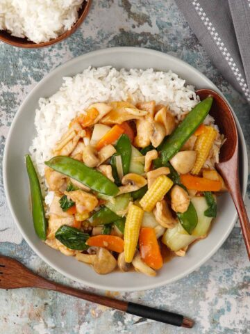 A grey plate with chop suey chicken on the bed of white rice with wooden spoon in the plate, with a small bowl of white rice.