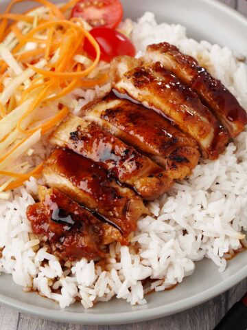 Japanese grilled teriyaki chicken on the bed of white rice and carrot and cabbage salad on the side.