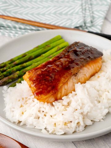 Japanese Teriyaki grilled salmon on the bed of white rice and grilled asparagus on the grey colour plate.