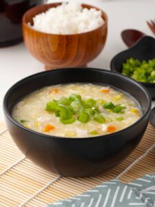 A black bowl full of Chinese style egg and corn soup, topped with spring onion in the foreground and a small wooden bowl of white rice in the background.