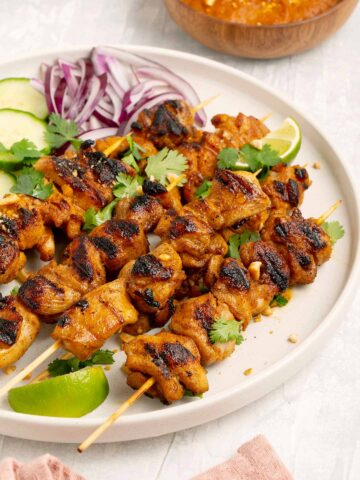 A big plates of grilled chicken skewers with lemon wedges to garnish.