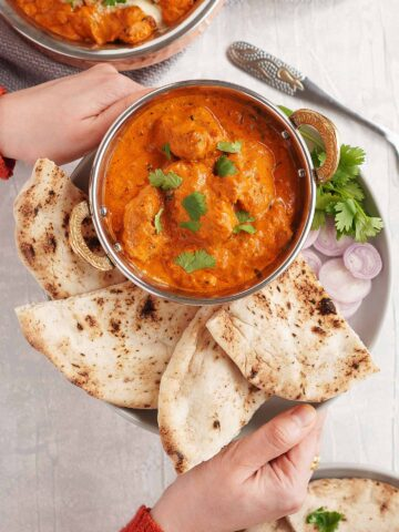 curry served with naan on the plate and sliced onion and coriander.