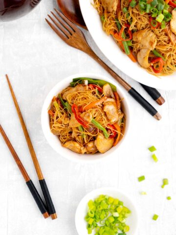overhead image of stir fry rice noodle in a white bowl with woodern cutlerly and a small bowl of green onions to garnish.