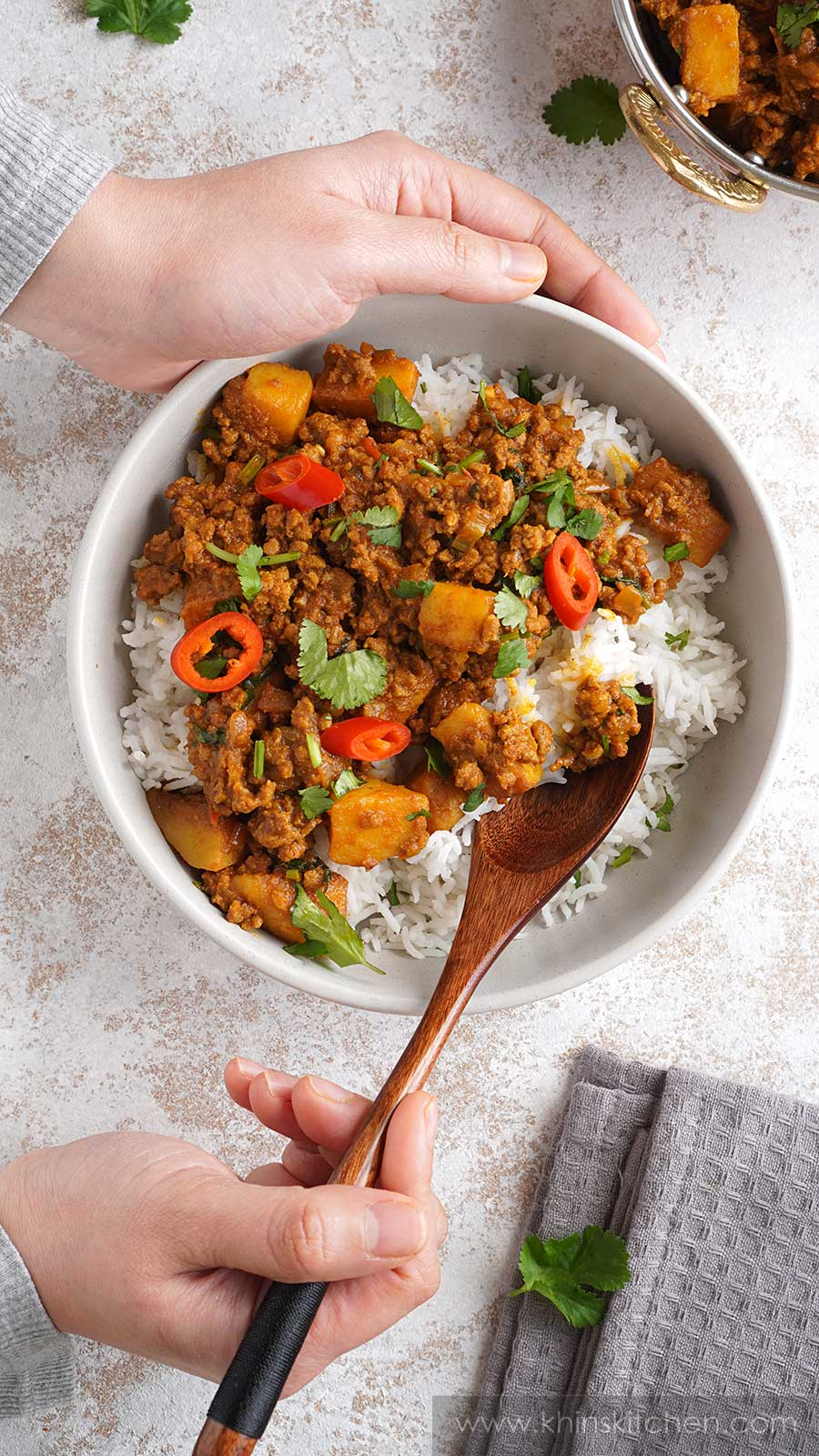 Ground beef curry,  cooked basmati rice in a cream colour bowl. Wooden spoon holding rice and minced beef.