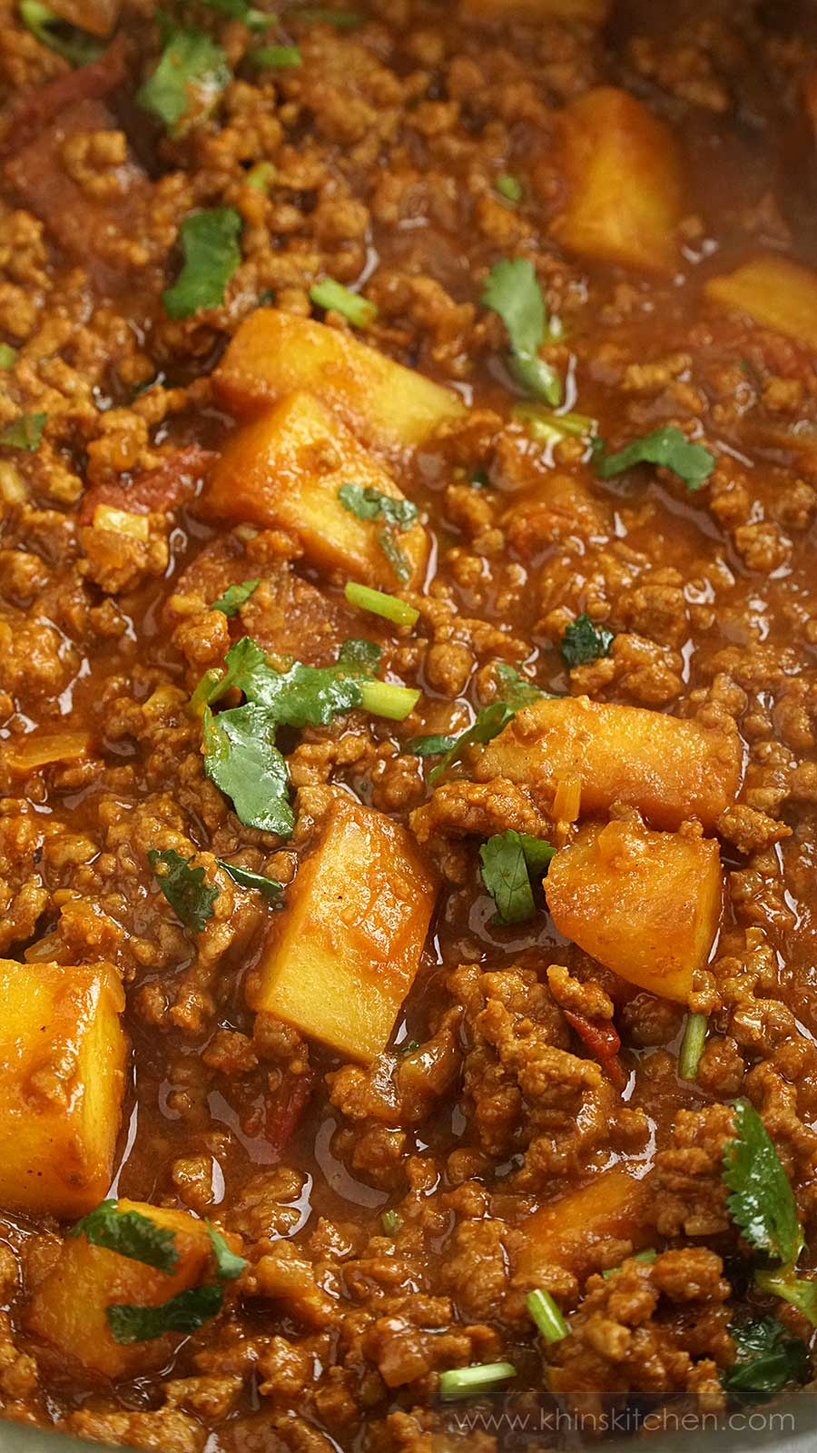 Close up shot of beef keema curry with small potato cubes, coriander.