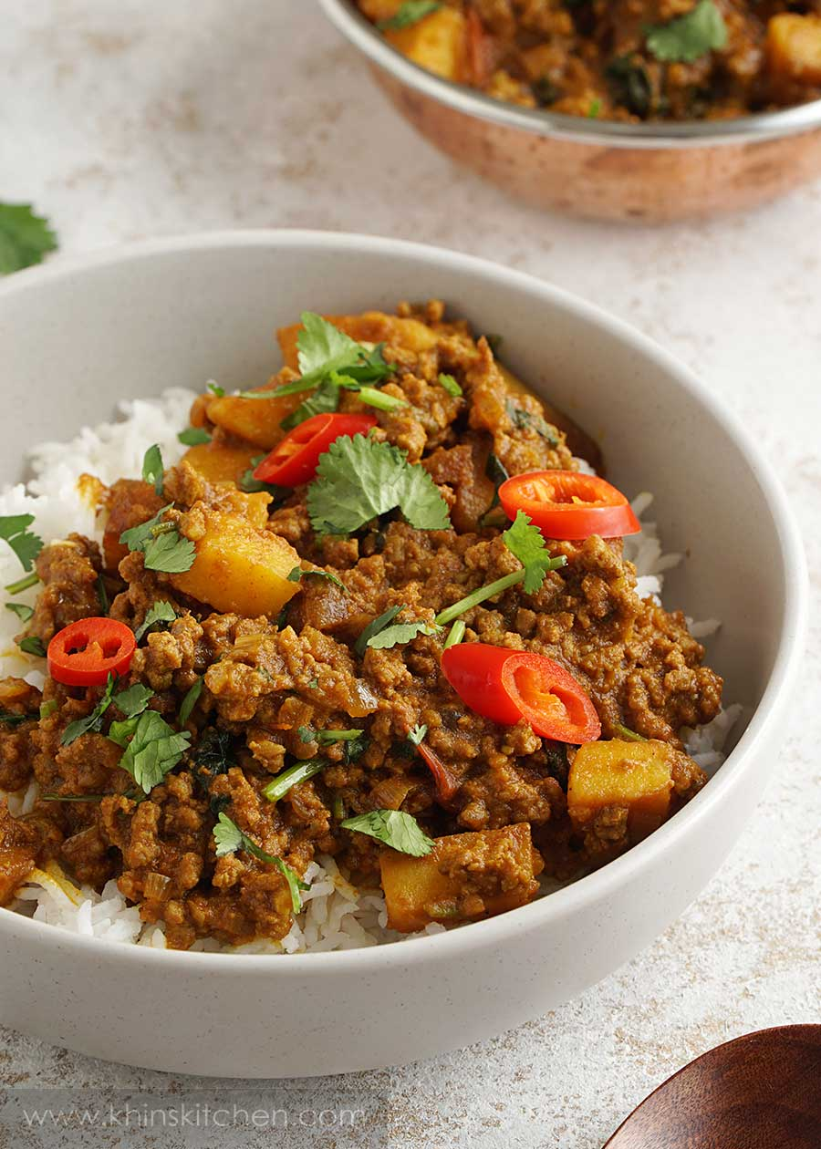 minced beef curry served over white rice in a cream colour bowl