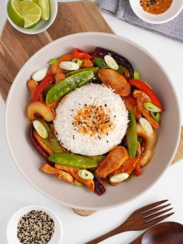 spicy chicken stir fry topped with plain rice with wooden cutlery on the side and lime wedges and sesame seeds to garnish at the side.