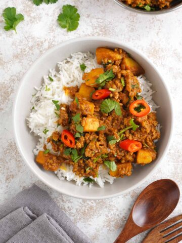 a bowl full of white rice topped with beef curry with wooden cutlerly with sprinkle coriander leave at the side.