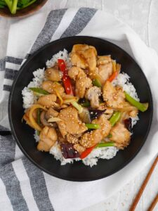 a plate full of white rice topped with stir fry chicken with wooden chop stick at the side.