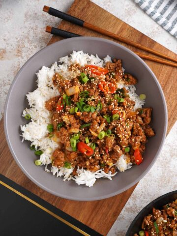 a grey plate full of white rice topped with ground beef style stir fry sit on the wooden chopping board with wooden chop stick.