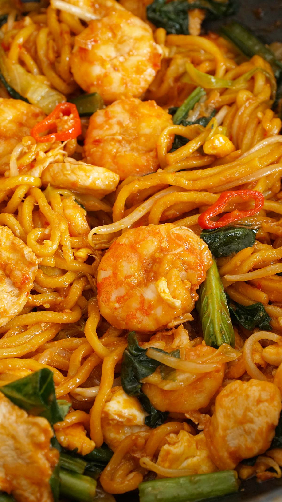 Stir fry yellow egg noodles with prawns, chicken slices, and vegetables.