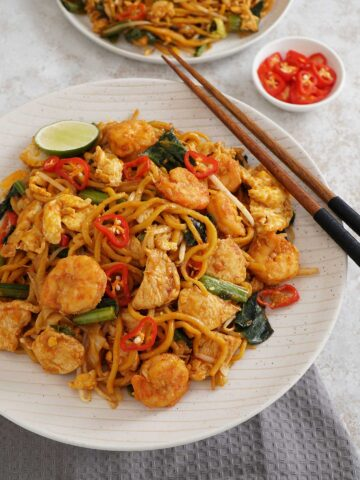 A plate filled with indonesian stir fry noodles, chicken prawns with wooden chop stick on the right side of the plate and a small bowl of sliced chilli to garnis at background.
