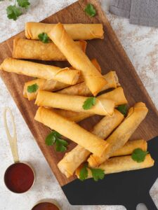 Thirteen spring rolls on the serving wooden boards with chilli dipping sauce.