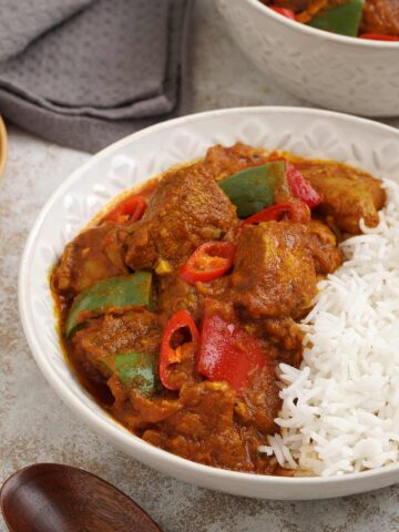 Close up photo of chicken jalfrezi and white rice with wooden chop stick in the foreground.