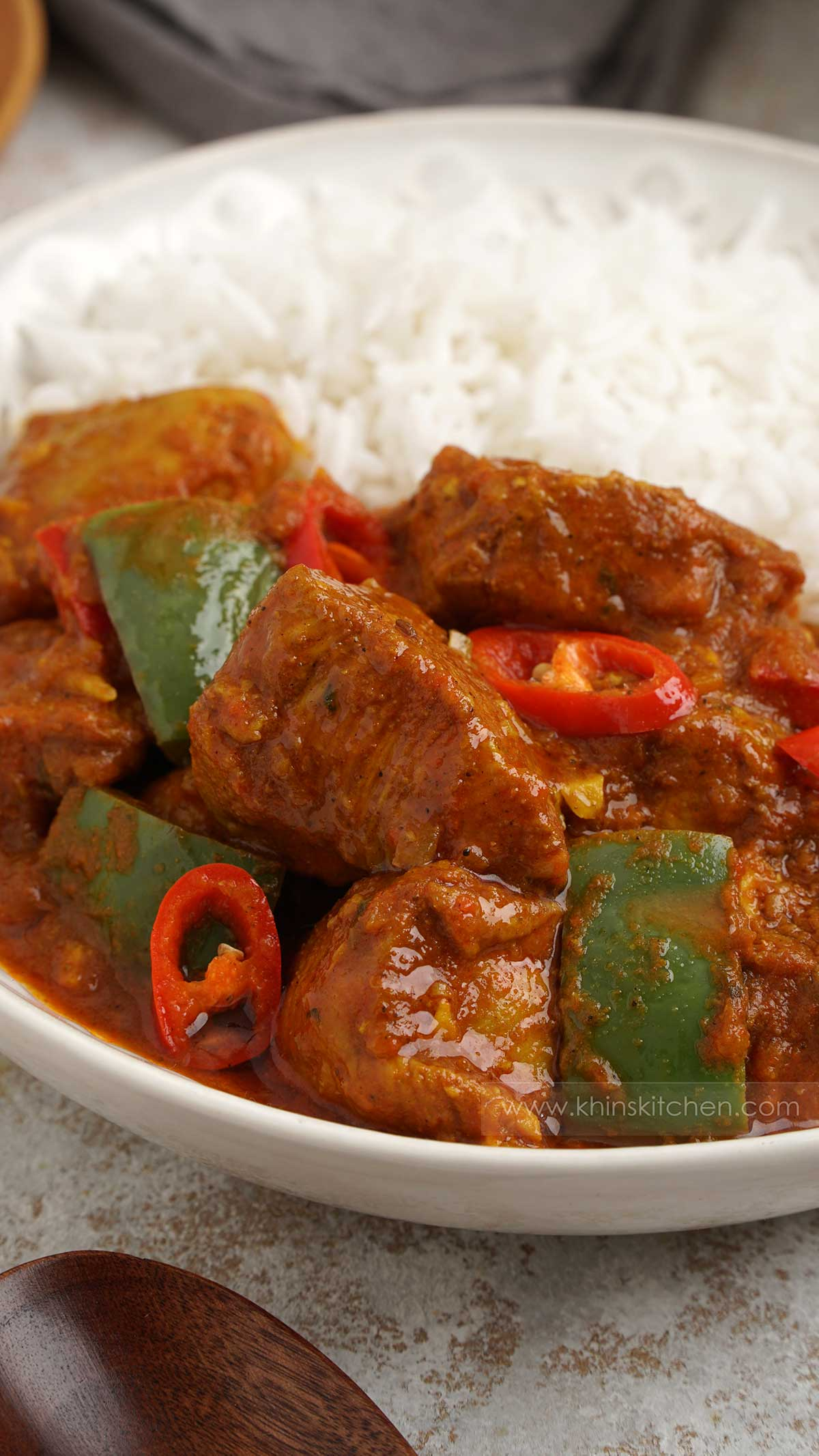 Close up shot of chicken curry with peppers and chilli slices, white rice at the background.