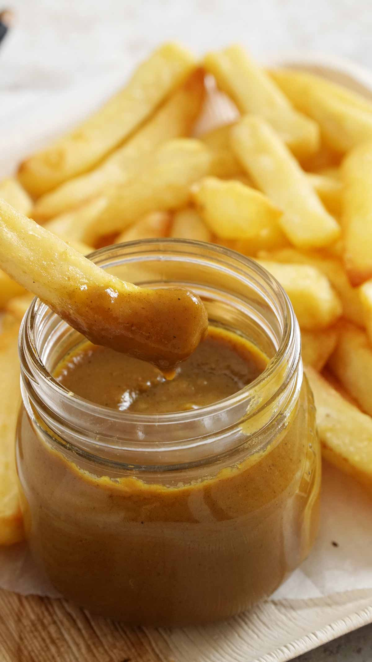 Close up view of chip is being dipped in the chinse curry sauce.
