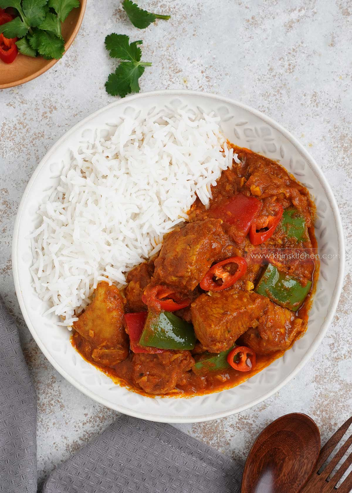 A white plate containing plain rice and chicken jalfrezi curry displayed on the white table.