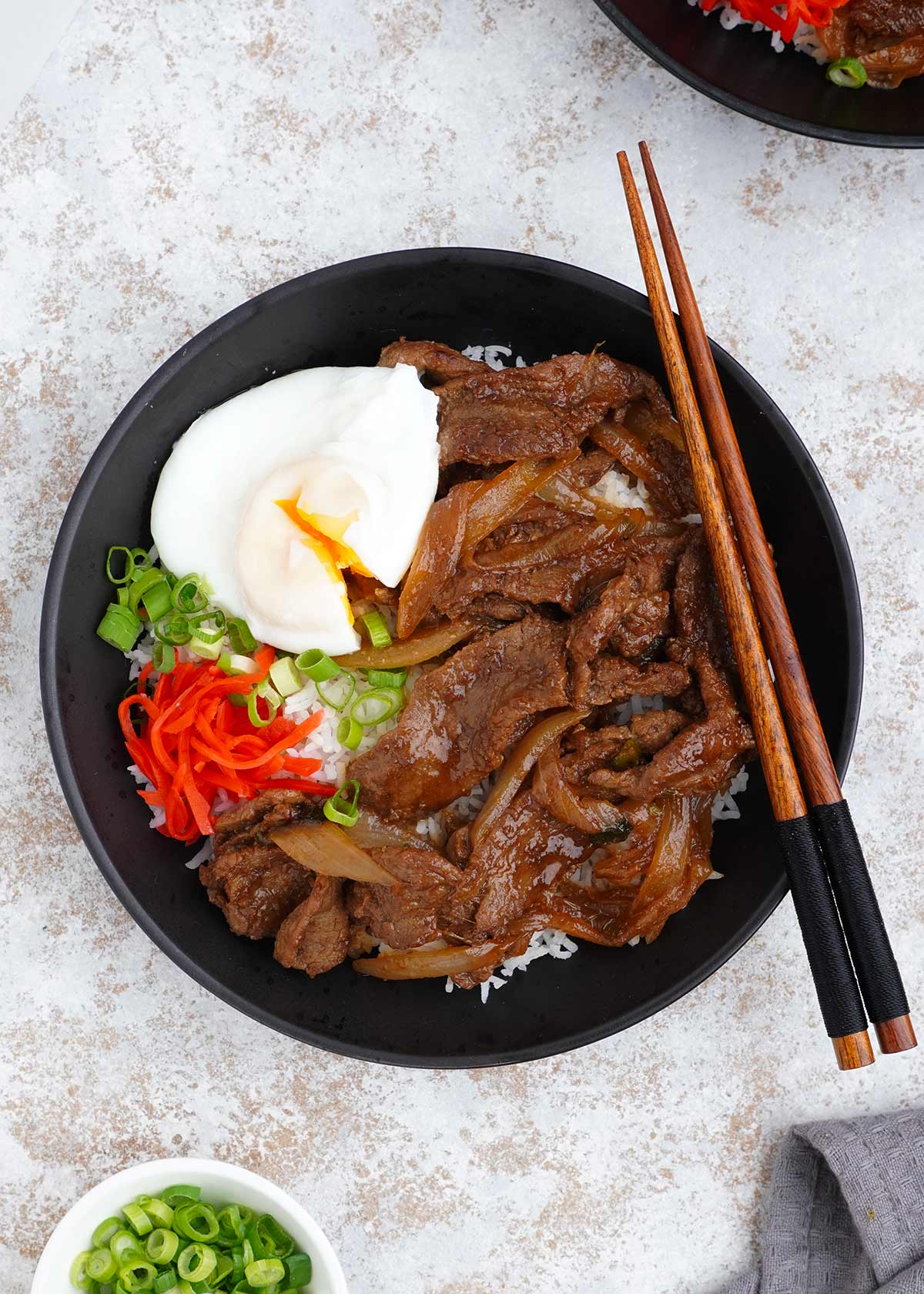 A black bowl filled with japanese beef with wooden chop side on the side.