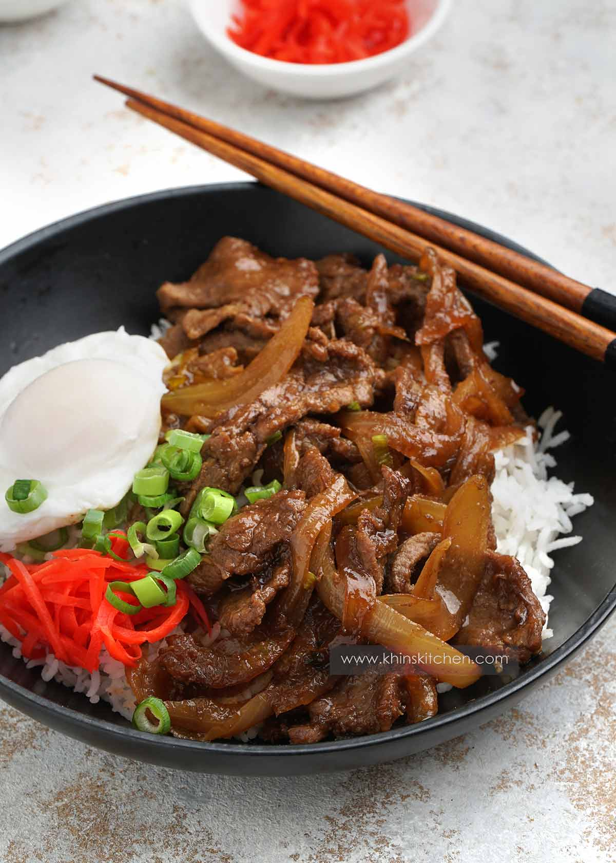 A bowl of japanese style beef stir fry with egg on the side and pickle.
