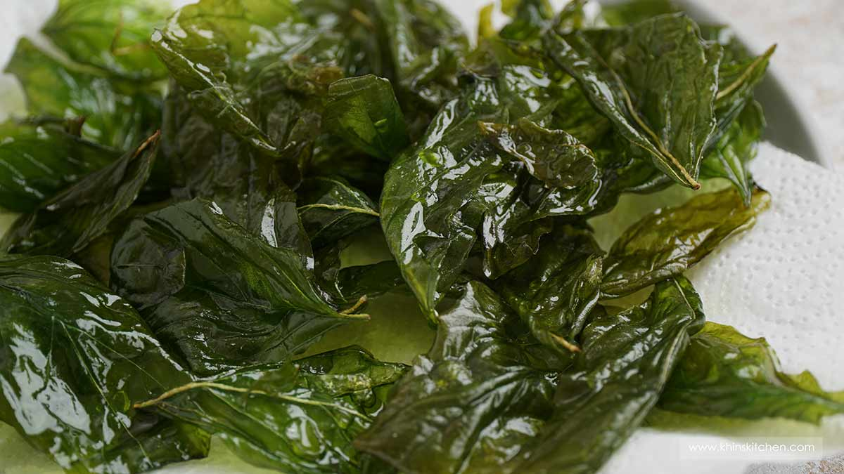 Fried basil leaves on the white kitchen towel.