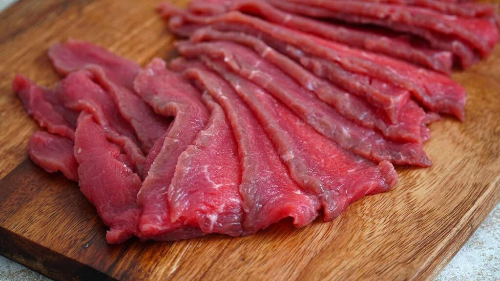 Thin slices beef on the wooden chopping board.