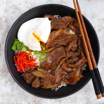 japanese stir fry beef on the white rice with a side of poached egg and spring onions