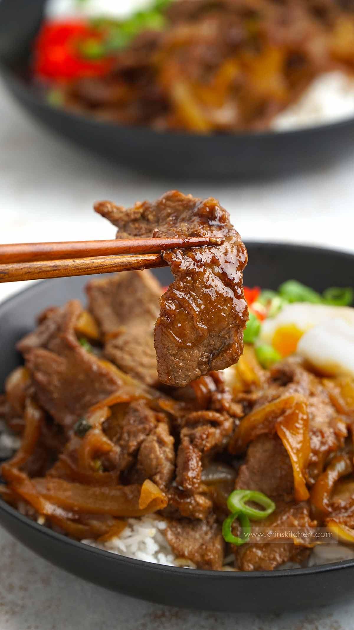 Wooden chop stick holding stir fried japanese beef.