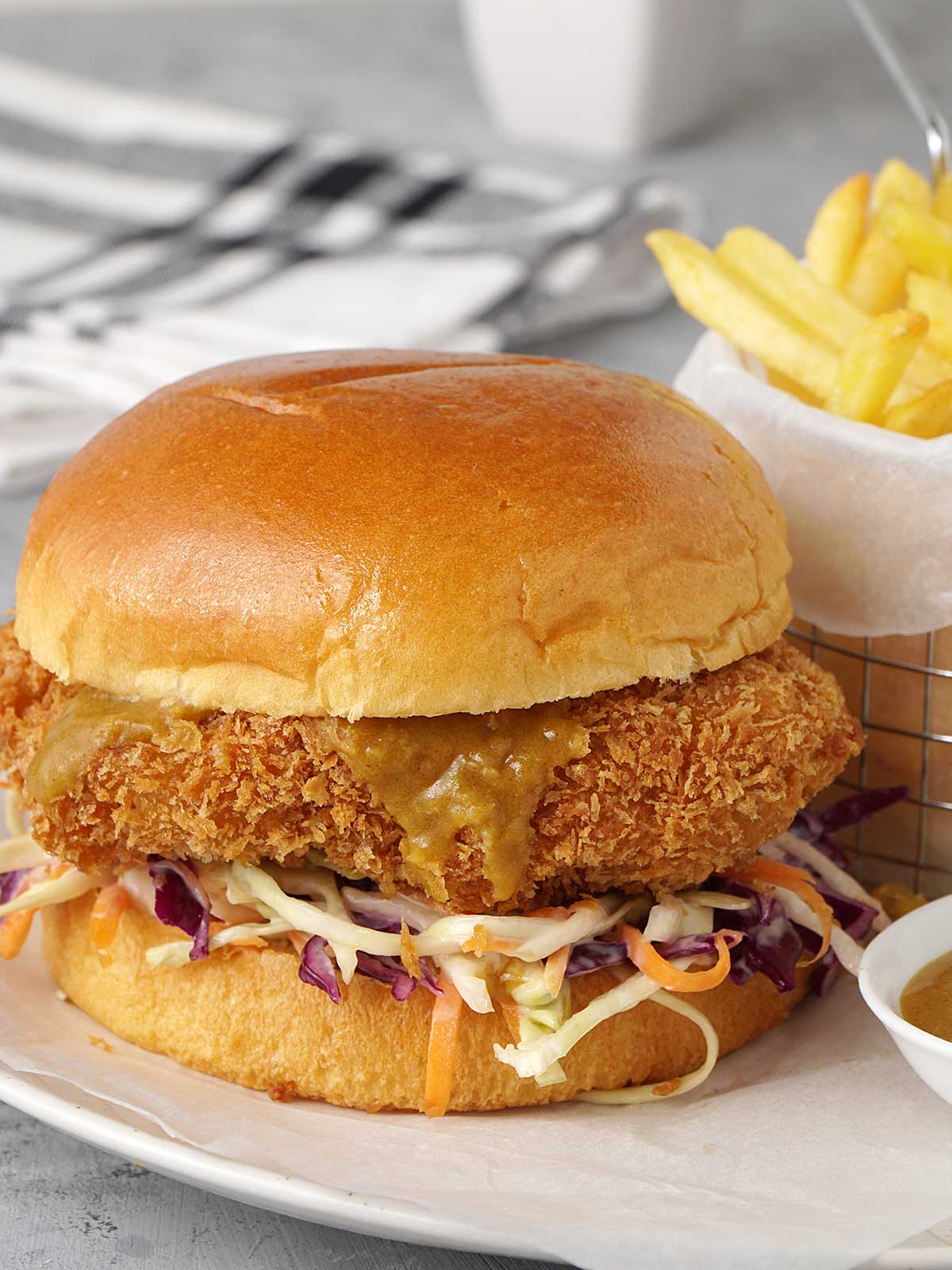 burger on the plate with a small bowl of curry sauce and chip basket in the background.