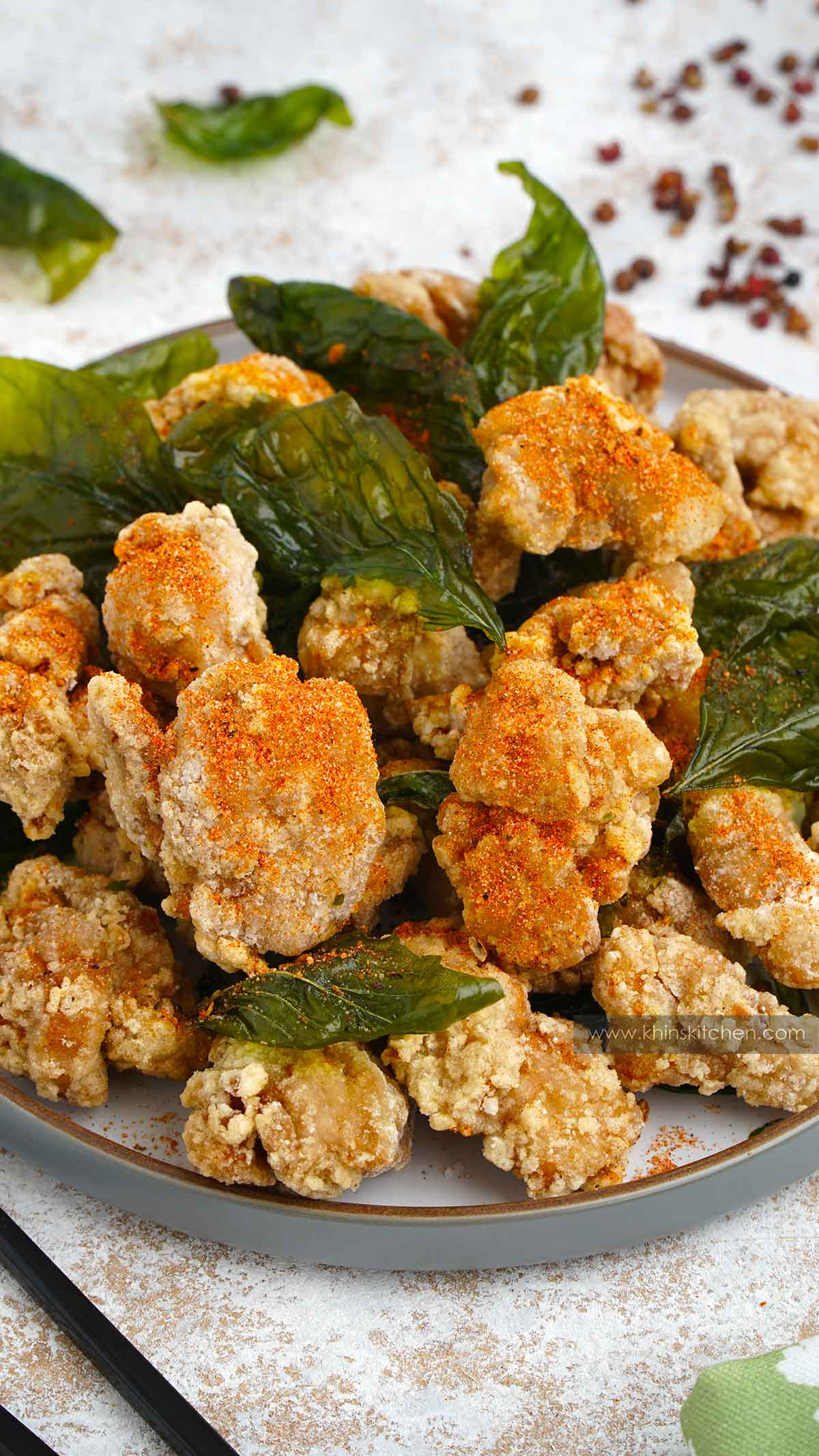 A close up shot of grey plate filled with Taiwanese fried chicken and basil leaves.