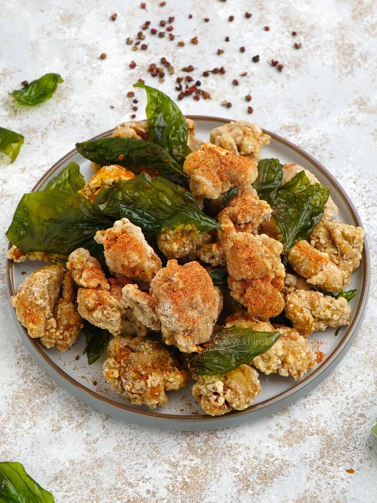 Taiwanese popcorn chicken with basil leaves in the grey plate.