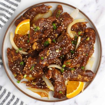 A plate full of crispy shredded beef and black and white strip napkin on the left side.