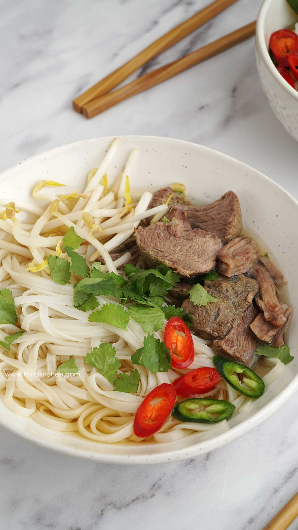 close up view of beef noodles soup in the white bowl.