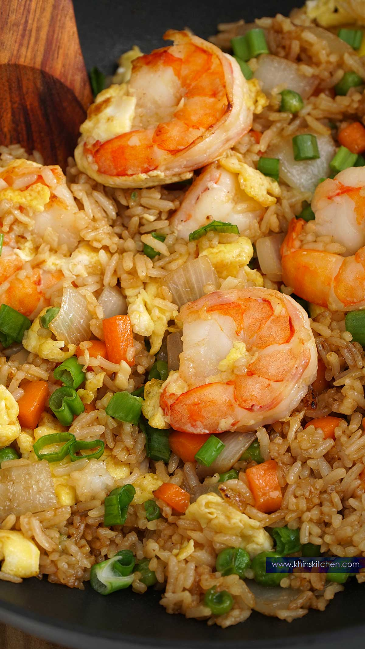 A close up view of rice, shrimp in the wok with wooden spatula.