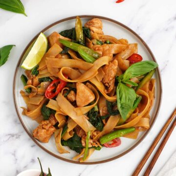 a plate full of thai noodles stir fry with wooden chopstick at the side.