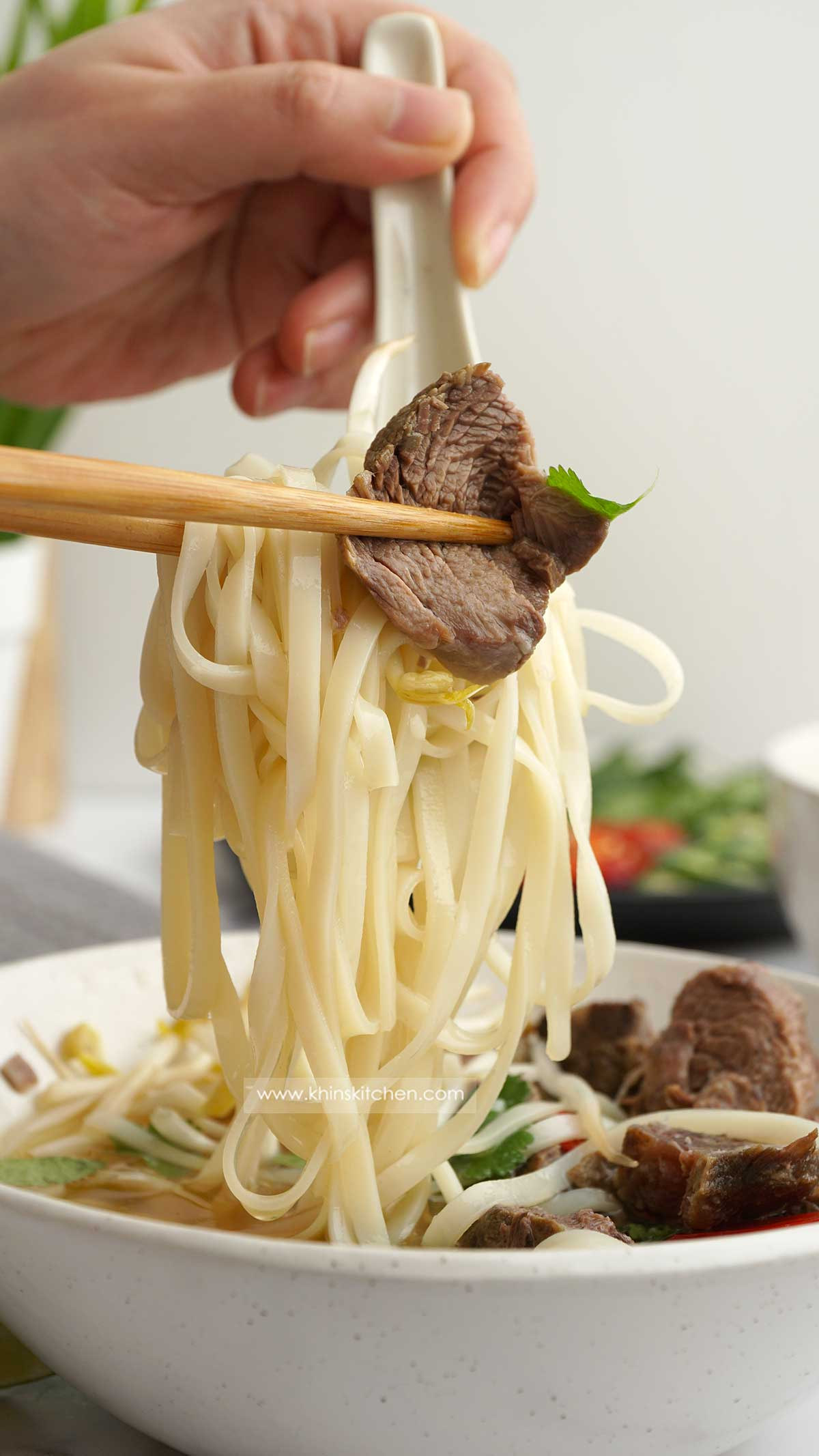 Rice noodles and beef are being hold with chop stick and soup spoon.