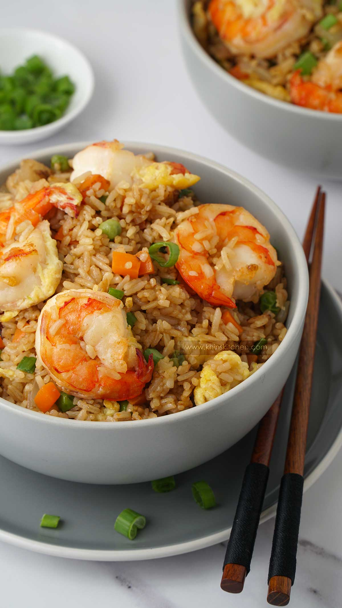 Rice, king prawns, vegetables in the grey bowl with wooden chop stick on the side.
