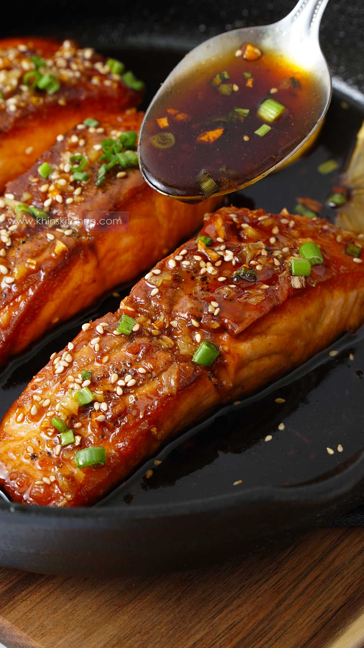 A skillet filled honey garlic salmon and sauce drizzling from spoon.
