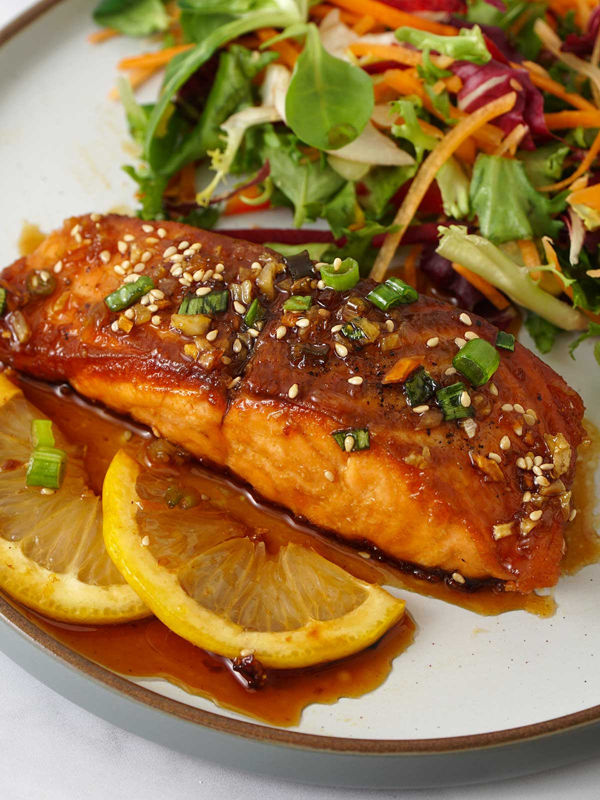 Honey salmon salmon, with two slices of lemon and a side of salad on the white plate.